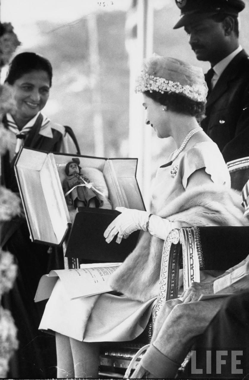 Queen Elizabeth II presented with a turbaned doll, a Girl Guide gift to her son Prince Andrew.