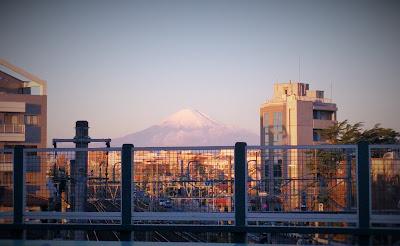 歩道の上から大きく見える、朝焼けの中の富士山。