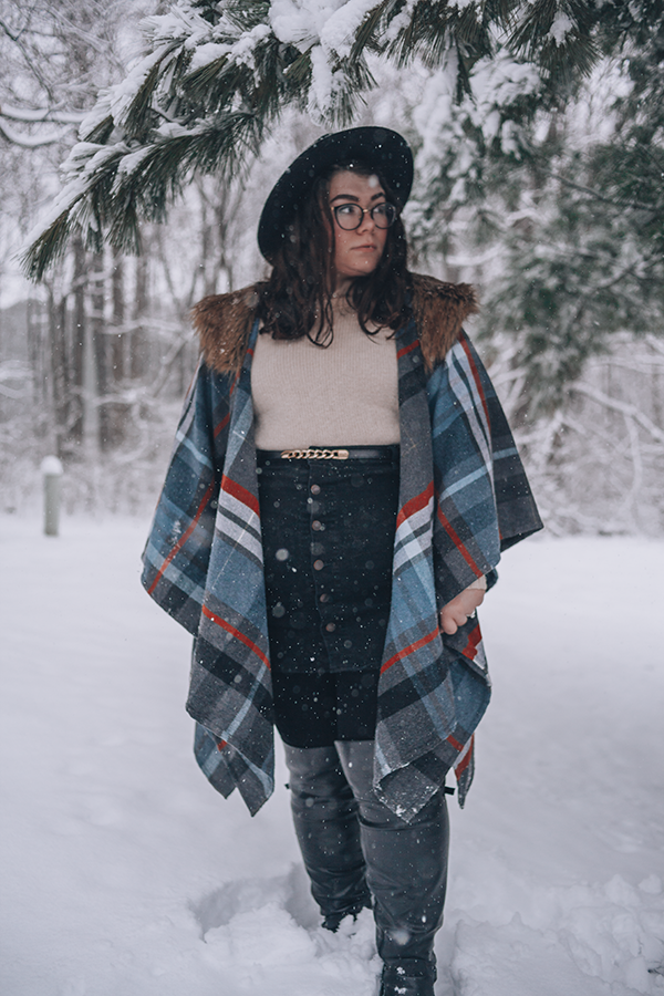 An outfit of a black wide brim hat, gray, red, and blue plaid shawl with brown faux fur collar, cream sweater, black button up mini skirt, and black over the knee boots in snow.