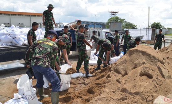 SIGAP : Para personil Lanud Supadio bergerak cepat melakukan pemasangan tanggul pasir di sisi runway.  Foto Kapentak Danlanud Supadio