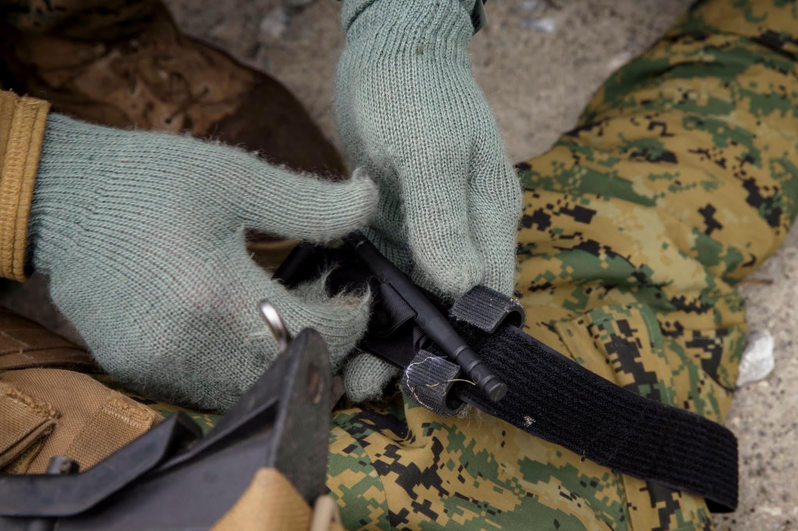 Gloved hands put a tourniquet on an upper thigh