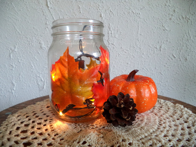 a jar with leaves and a string light in it