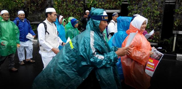 Aksi 112 Atribut Muslim Serba Putih Berganti Jas Hujan Plastik Warna-warni
