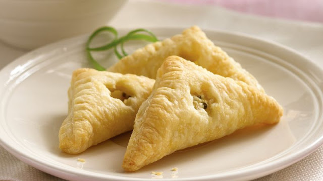 Form frozen puff pastry into triangles filled with a Mediterranean Feta Cheese, Lemon and Chive Turnovers Recipe