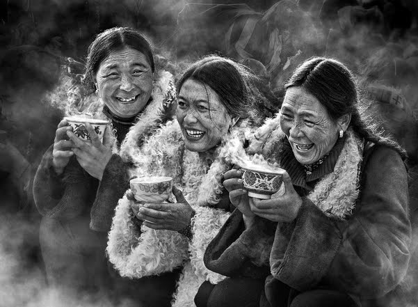 Beautiful black and white photo of three friends, old asian ladies laughing and drinking hot tea outside