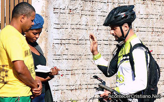 Misionero reparte biblia en bicicleta