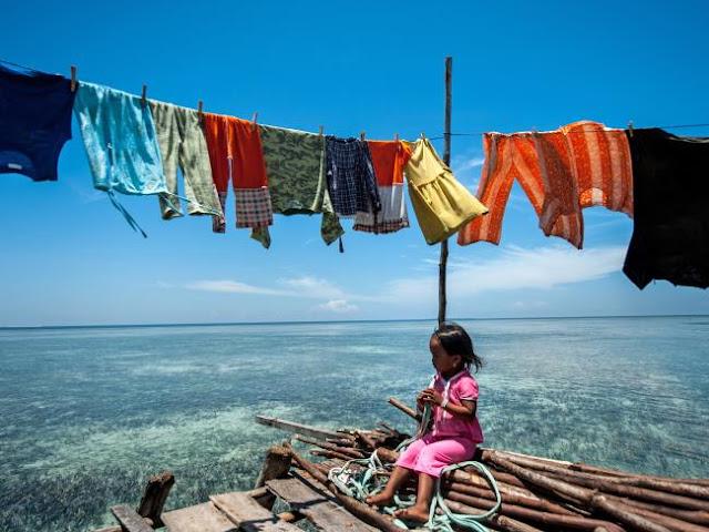 Ng Choo Kia - Menina sentada em pilhas de madeira em sua casa sobra a agua, os Bajau praticamente não tem acesso a terra firme, podendo contar apenas com algumas micro ilhas ao longo de seu território