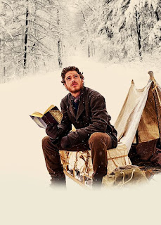 A hot guy reading a book in the snow