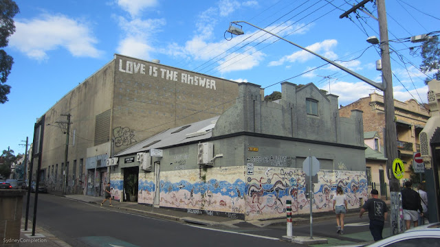 "Aboriginal style street art on the side of a building, with another building behind saying ""Love is the answer"""