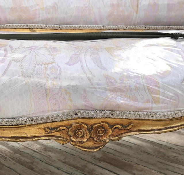 vintage french settee covered in plastic