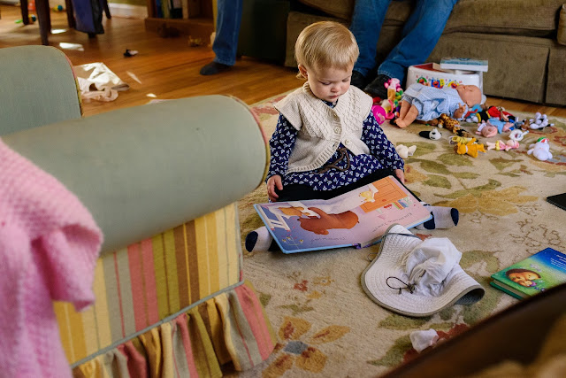girl reading book on rug, surrounded by toys © Diana Sherblom Photography