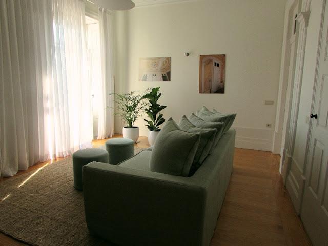 sofá e pufs numa sala de apartamento