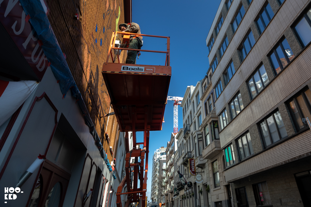 Artist Case Maclain at work in a scissor lift on his Ostend Mural