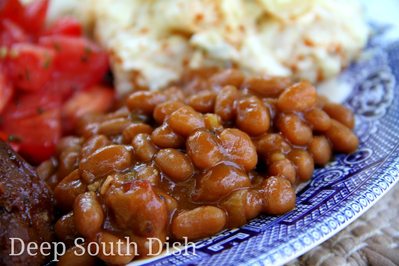 Southern seasoned baked beans with chili sauce, mustard, brown sugar, bacon, onion and bell pepper - they're a cookout tradition! Pictured here with grilled ribs, Mama's Southern potato salad and marinated tomatoes.