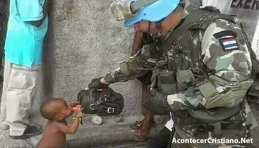 Soldado da de beber agua a un niño en Haití