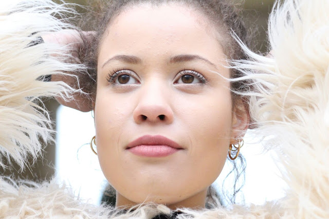 A close-up image of Eboni posing in an Apricot Clothing long haired jacket
