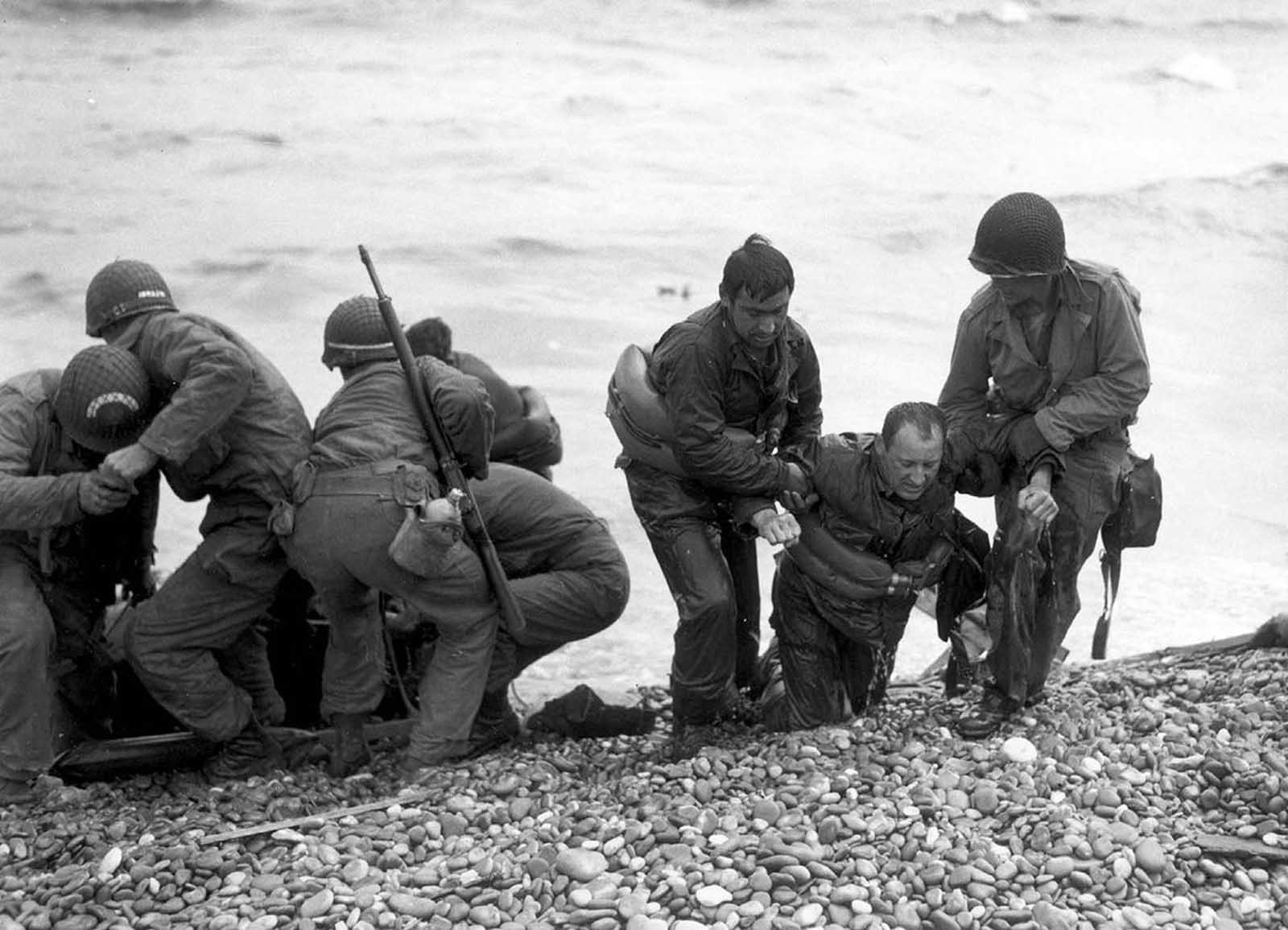Members of an American landing party help others whose landing craft was sunk by enemy action of the coast of France. These survivors reached Omaha Beach by using a life raft on June 6, 1944.