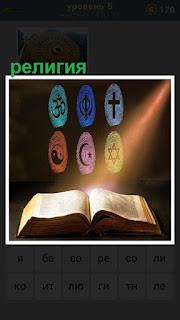 На столе раскрытая книга и на стене символы, относящиеся к религии
