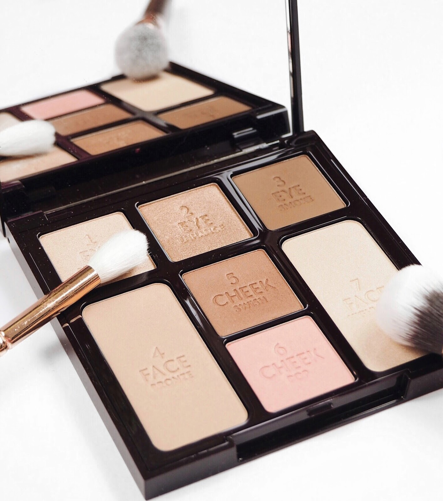 Charlotte Tilbury Beauty Glow Look In An Instant Palette close up, with rose gold and bronzed eyeshadows, and rose gold Zoeva makeup brushes on a white background as a flatlay for a UK beauty blog review