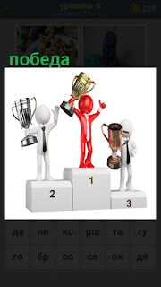 На пьедестале на трех местах стоят победители с кубками
