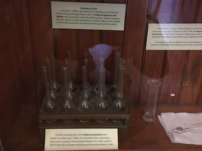Image is of test tubes inside a wooden case . The tubes are flared at the base.