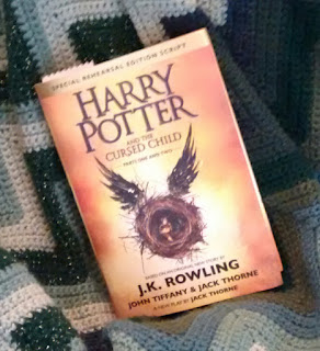 Hardcover bound script of 'Harry Potter and the Cursed Child' placed on green-ripple afghan