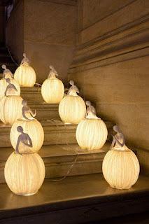 Uma dupla de artistas franceses formada por Sophie Mouton-Perrat e Frédéric Guibrunet cria, entre outras, sensacionais esculturas-luminárias feitas de nada menos que papel machê.Descrição: Em um canto de uma escadaria de mármore sobre cinco degraus, nove luminárias acesas distribuídas duas a duas em cada degrau debaixo para cima, sendo a última, na parte central, no topo. As delicadas luminárias têm a forma de bailarinas com a saia bem rodada em forma de balão gomado, cada bailarina tem uma expressão gestual e remetem às de caixinha de música.