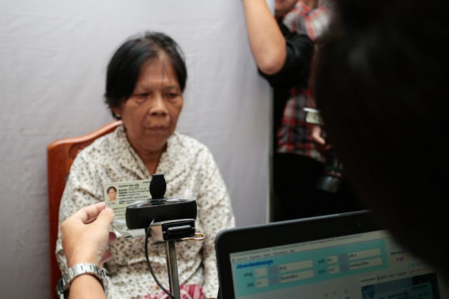 A woman has her photo taken earlier this month as her identification is verified at a voter registration office. Heng Chivoan