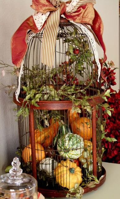 This vintage bird cage filled with pumpkins is a great way to decorate for autumn.