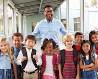 image of a young, male school teacher surrounded by grade school children