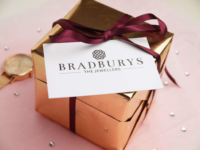 a rose gold cube with a purple ribbon and a white business card reading 'bradburys the jewellers' in silver
