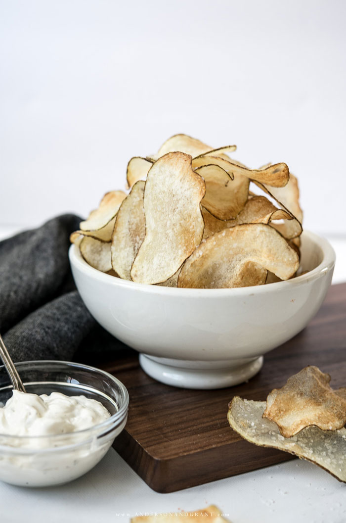White bowl of potato chips and bowl of dip