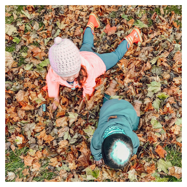 boy and girl playing in fall leaves