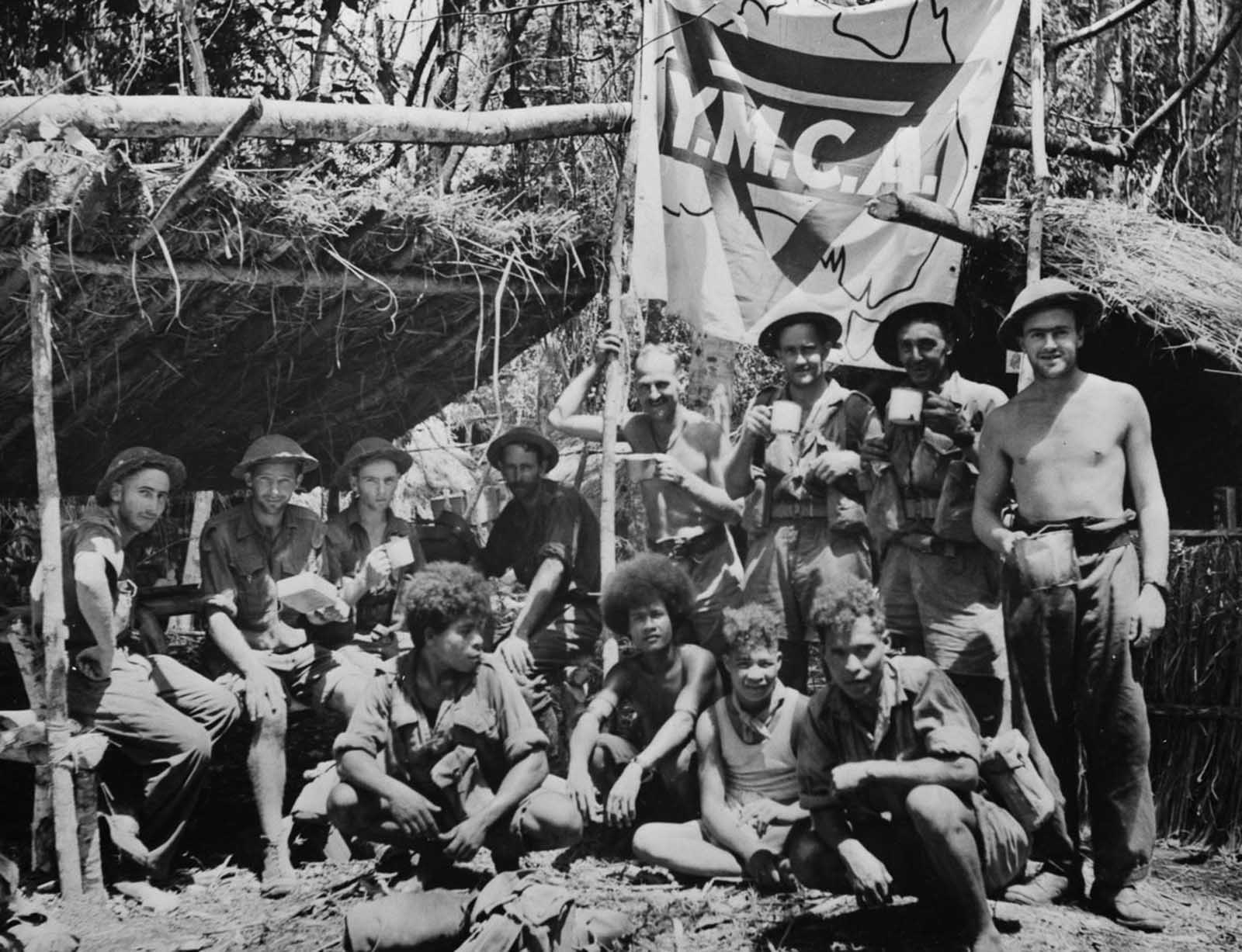 Natives and Allied troops rest during the New Guinea offensive.