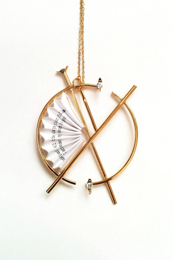 golden circular necklace with folded paper fan