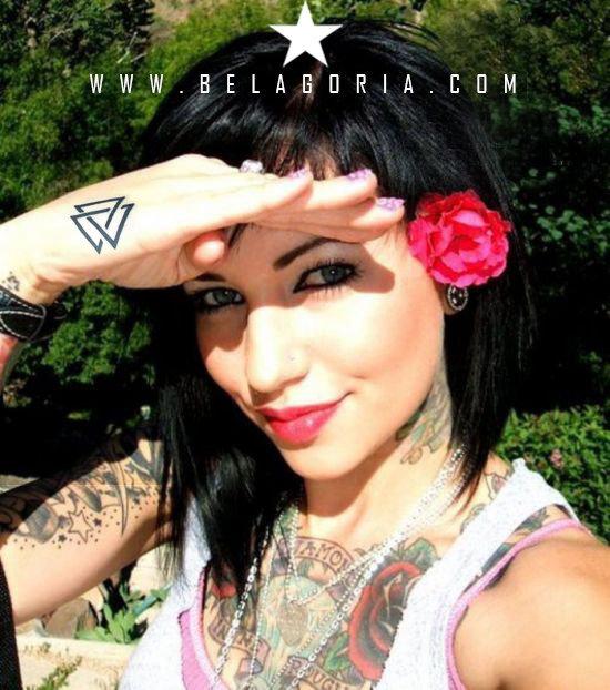 Vemos chica tapándose del sol, lleva en el dorso un tatuaje de valknut