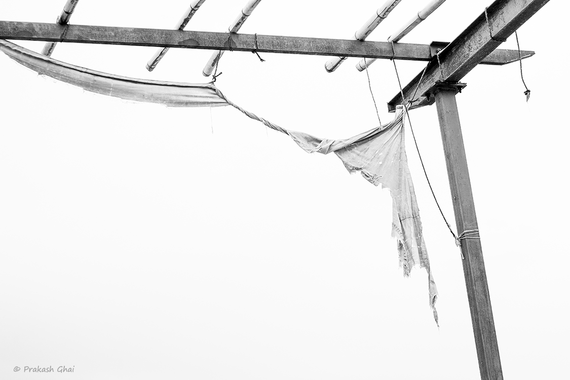 A Black and White Minimalist Photo of a Torn cloth hanging over an old wooden thatch roof