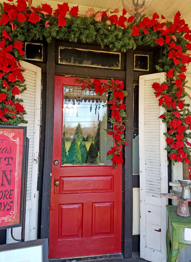 red door decorated for Christmas with poinsettias around it on the porch