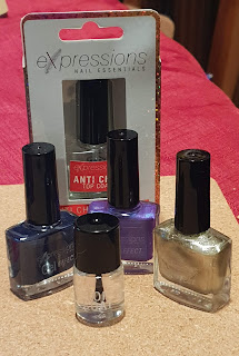 Three regular size bottles of Expressions nail polish in dark blue, purple and gold, with a smaller bottle of top coat in front and a box with a larger bottle of top coat behind.