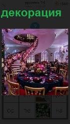 В просторном помещении круглый стол и винтовая лестница поднимается на верх, художественно украшено декорацией