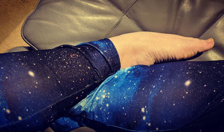image of my folded legs, clad in space-themed leggings