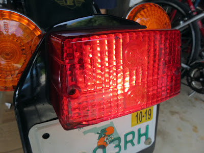 Brake light at back of Royal Enfield is illuminated.