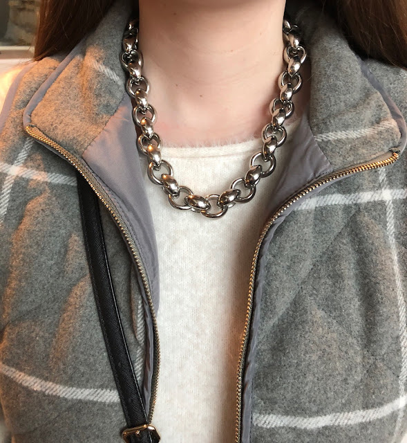 Model is wearing grey vest with white sweater and black and silver accessories.