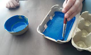 As mãos de um aluno a pintar de azul uma caixa de ovos que será o presépio