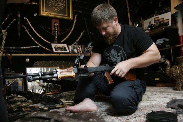 Sentado no chão segurando um rifle de guerra,com várias armas e munições espalhadas no chão