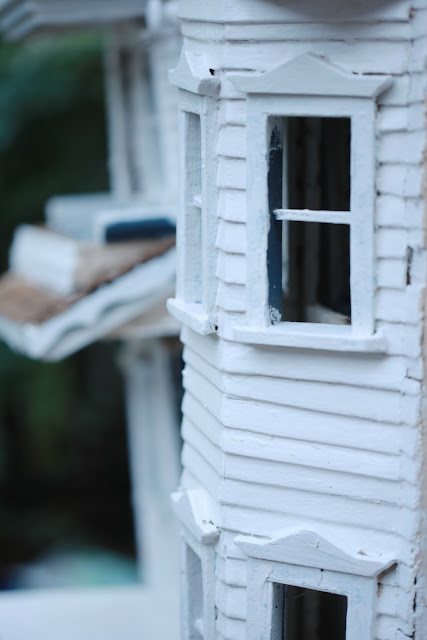 white siding and vintage details on dollhouse