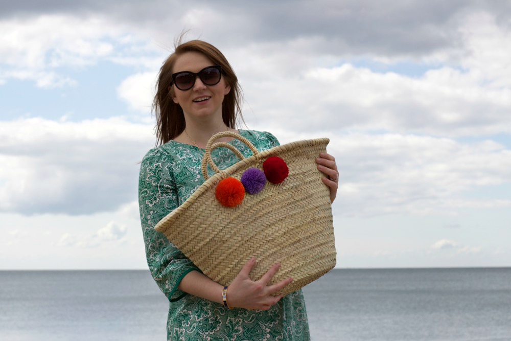 lauren in boden with her moroccan pom pom woven basket bag from postcards home