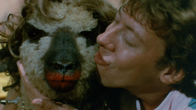 Melvin is about to kiss a goat with lipstick on