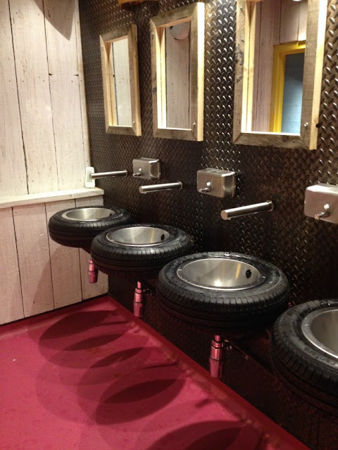 sinks are tyres and the floor is bright pink with white washed wooden walls