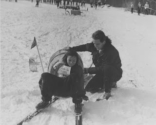A black and white photograph of a man crouched by a girl on skis.